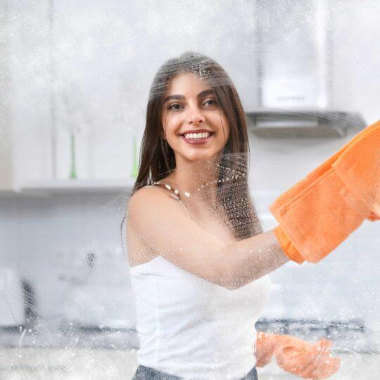 smiling-woman-washing-window-with-rag-min (1)